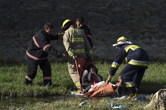 Des pompiers et des secouristes évacuent le corps... (AFP, Wakil Kohsar)