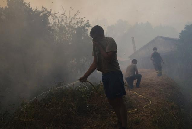 Des villageois tentent d'éteindre un feu avec un... (AFP)