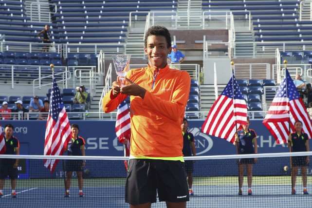 Félix Auger-Aliassime pose fièrement avec son trophée de... (Photo Mike Stobe, archives AFP)