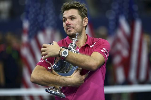 Le Suisse Stan Wawrinka étreint le trophée remis... (AFP, Jewel Samad)