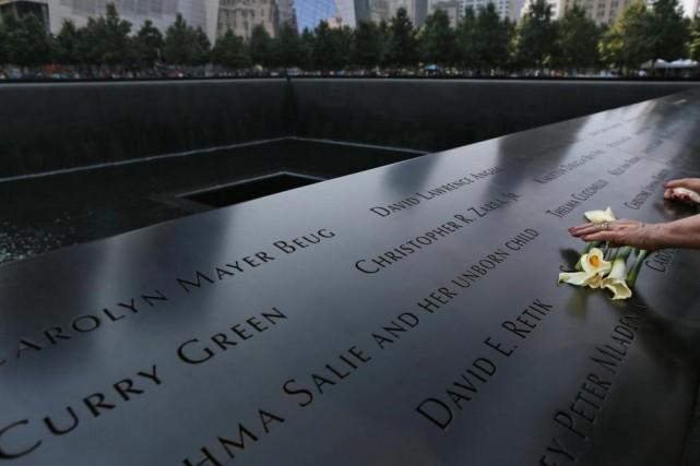 Une visiteuse dépose des fleurs sur le mémorial... (Photo Mary Altaffer, Associated Press)