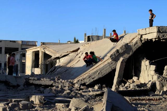 Des enfants syriens glissent dans les ruines d'un... (photo MOHAMAD ABAZEED, AFP)