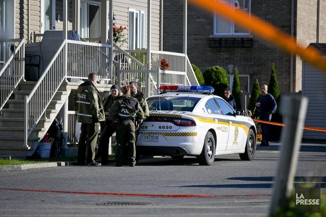 Des policiers surveillent l'arrière de l'immeuble où les... (PHOTO DAVID BOILY, LA PRESSE)