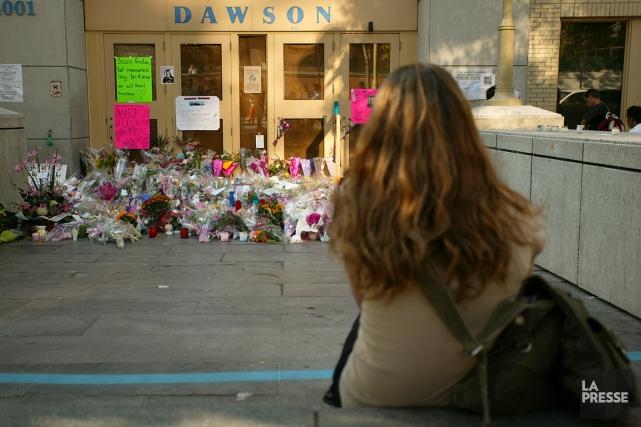 Une jeune femme se recueille devant le collège... (PHOTO DAVID BOILY, LA PRESSE)