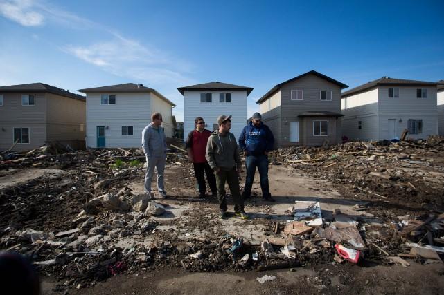 Des résidants posent devant leurs maisons dans le... (Photo Topher Seguin, REUTERS)