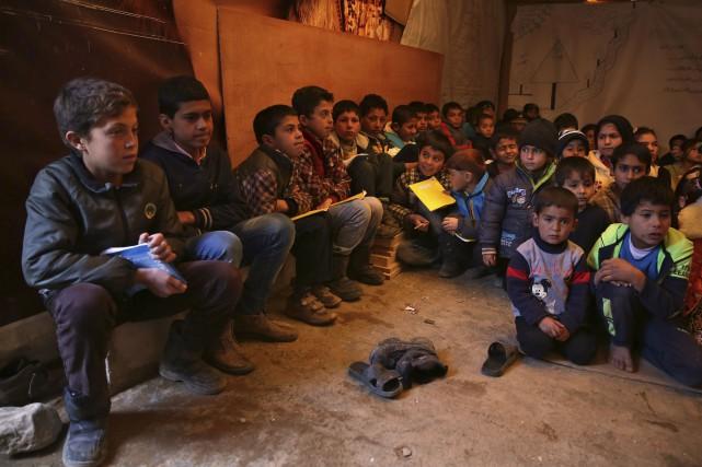 De jeunes syriens, assis sur le sol, écoutent... (AP, Bilal Hussein)