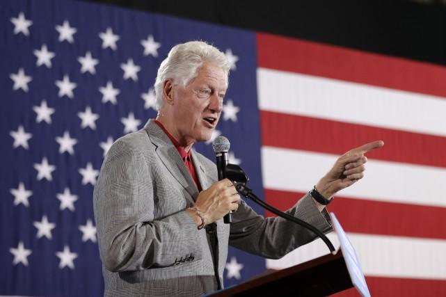 L'ancien président Bill Clinton aide sa femme Hillary... (AP, John Locher)