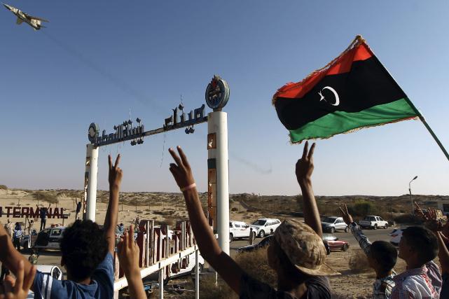 Des Libyens saluent un chasseur avec leur drapeau,... (AFP, Abdullah DOMA)