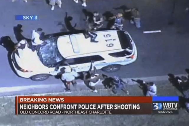 Une autopatrouille est prise d'assaut par des manifestants... (Associated Press)