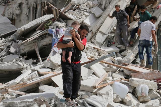 Un homme porte dans ses bras un bambin... (photo Abdalrhman Ismail, REUTERS)