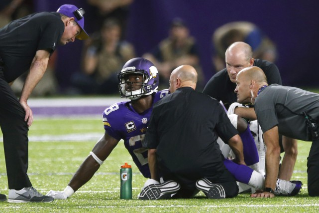 Adrian Peterson (28) s'est blessé durant le match... (Photo Jim Mone, AP)