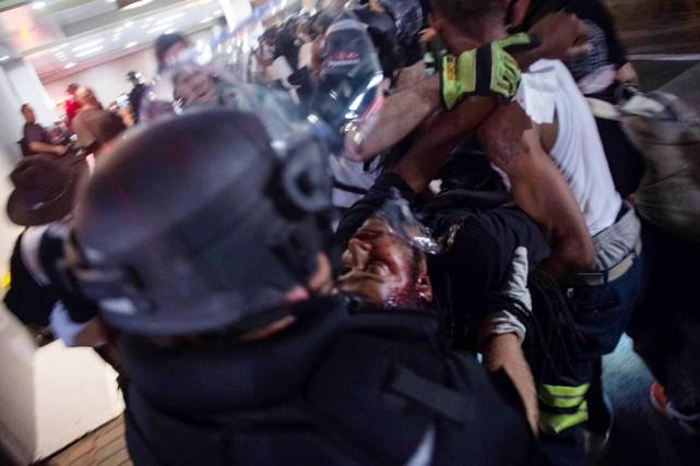 Des policiers et des manifestants transportent l'homme qui... (NICHOLAS KAMM, AFP)