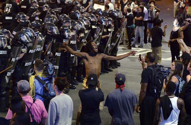Des policiers bloquent le chemin à des manifestants,... (AP, Jeff Siner)