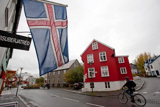 Un cycliste passe devant un drapeau de l'Islande... (Photo Paul Taggart, Bloomberg)