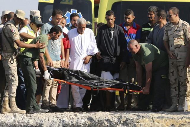 Des secouristes transportent le corps d'une des victimes... (MOHAMED ABD EL GHANY)