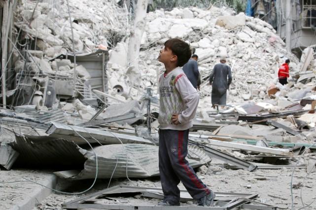 Un garçon examine les dommages causés dans sa... (photo Abdalrhman Ismail, REUTERS)