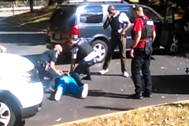 Des policiers entourent le corps inerte de Keith... (Image tirée de la vidéo, The New York Times)