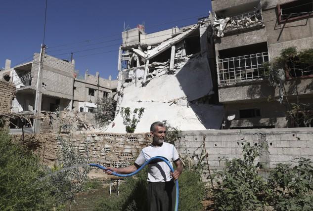 Un homme arrose ses plantes devant des bâtiments... (AFP)