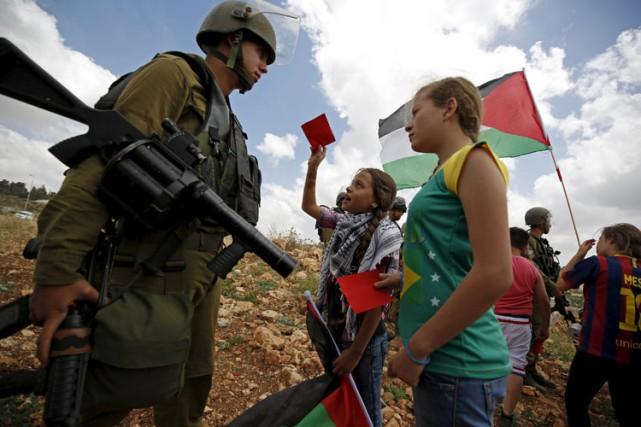 Des filles palestiniennes brandissent des cartons rouges devant... (ARCHIVES REUTERS)