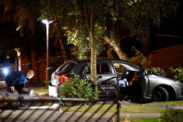 Un techniciendepolice examine une voiture dans laquelle se... (PHOTO AFP)