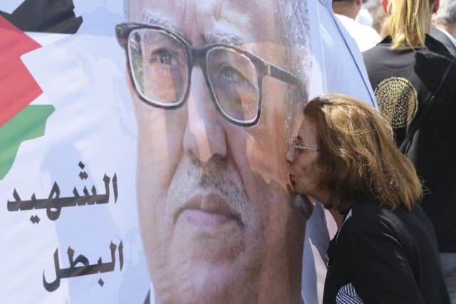 Une femme embrasse le portrait de Nahed Hattar.... (Photo Khalil Mazraawi, Agence France-Presse)