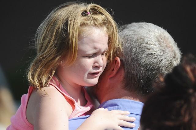 Cette petite fille était émue de retouver son... (AP, Rainier Ehrhardt)