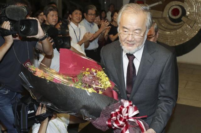 Le biologiste japonais Yoshinori Ohsumi reçoit des fleurs,... (Agence France-Presse)