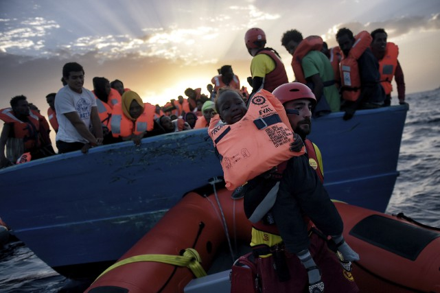 Un enfant est secouru par un travailleur humanitaire... (AFP, Aris Messinis)