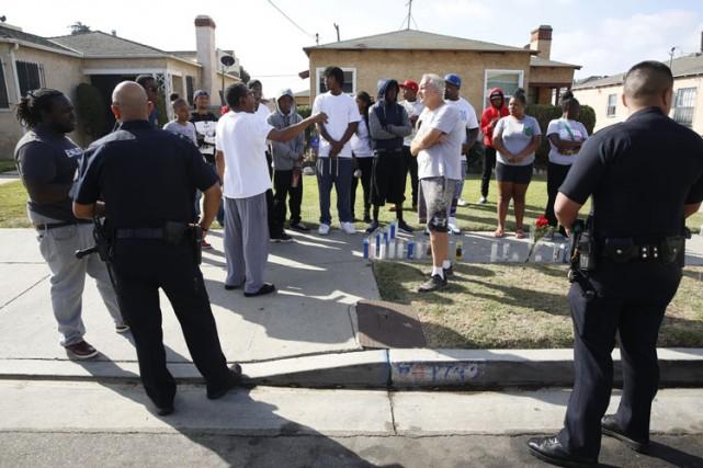 Des policiers discutent avec des gens réunis devant... (PHOTO AP)