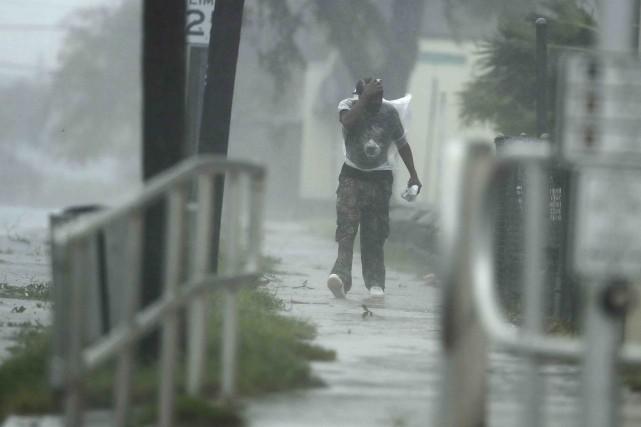 Un homme marche dans la tempête à Daytona... (AP, Charlie Riedel)