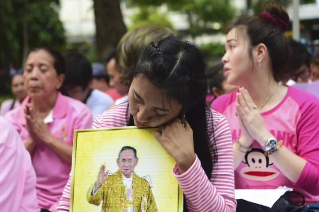 Des Thaïlandaises prient à l'extérieur de l'hôpital Siriraj,... (AFP, Munir Uz Zaman)