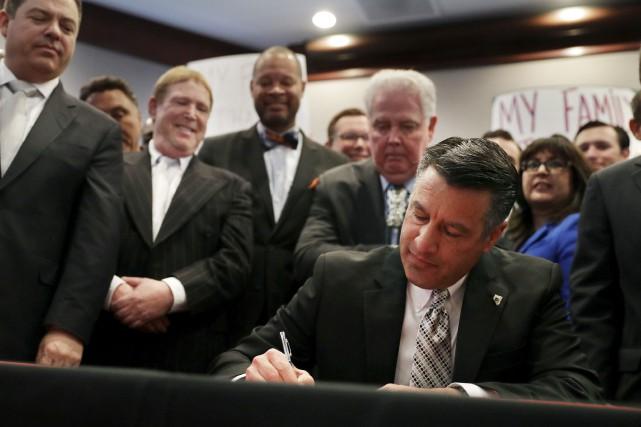 Le gouverneur du Nevada, Brian Sandoval, signe le... (AP, John Locher)