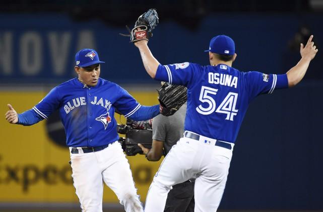 Ezequiel Carrera et Roberto Osuna célèbrent après avoir... (Nathan Denette, La Presse canadienne)