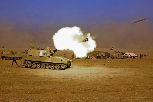 Un militaire irakien tire en direction du village... (photo  AHMAD AL-RUBAYE, AFP)