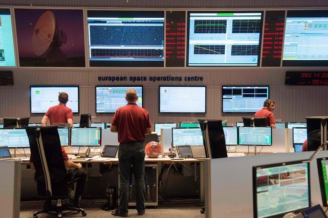 Des ingénieurs surveillent le module Schiaparellidepuis le Centre... (THOMAS KIENZLE, AFP)