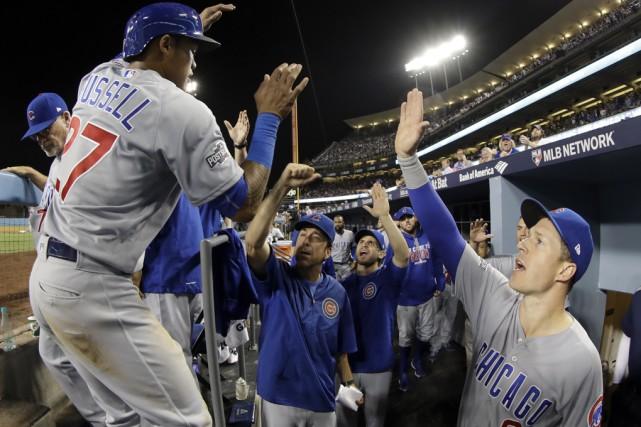 Les joueurs des Cubs félicitent Addison Russell en... (David J. Phillip, Associated Press)