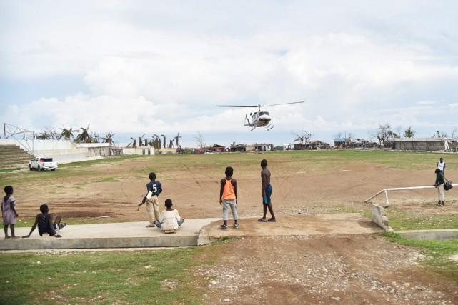 Des enfants regardent un hélicoptère atterrir sur le... (photo HECTOR RETAMAL, AFP)