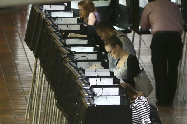 Des électeurs enregistrent leur vote en vue de... (PHOTO LYNNE SLADKY, AP)