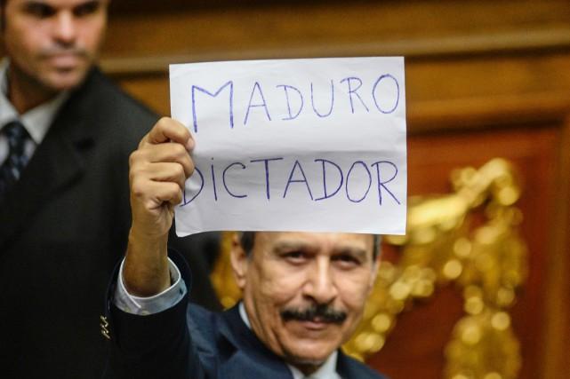 Un député de l'opposition brandit une feuille sur... (photo FEDERICO PARRA, AFP)