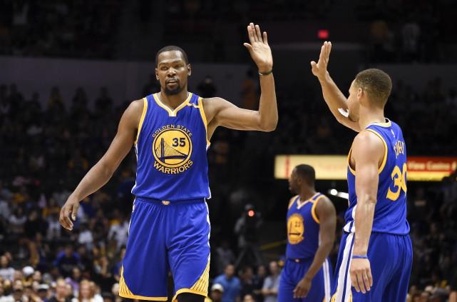 L'arrivée du joueur vedette Kevin Durant (à gauche)... (AP, Denis Poroy)