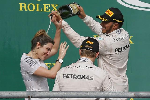 Lewis Hamilton, à droite, a offert une douche... (AP, Tony Gutierrez)