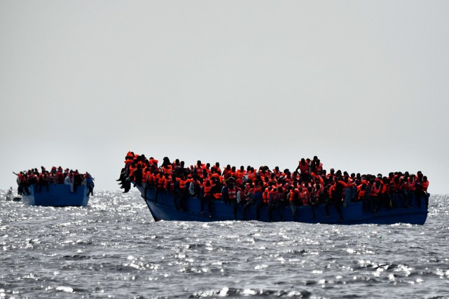 Des migrants attendent à bord d'embarcation d'être secourus,... (photo ARIS MESSINIS, archives AFP)