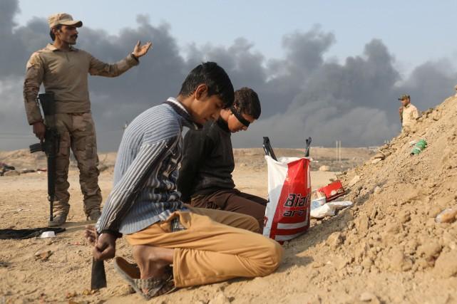 Un soldat irakien surveille deux détenus accusés d'être... (REUTERS)