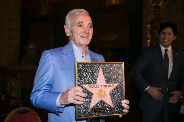 Charles Aznavour pose avec son étoile honorifique, remise... (Photo JONATHAN ALCORN, AFP)