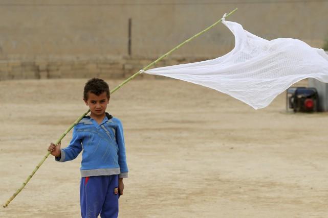 Drapeau blanc à la main, ce jeune Irakien... (AFP, Ahmad Al-Rubaye)