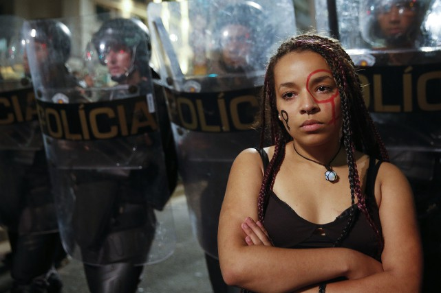 Une femme devant des policiers antiémeute lors d'une... (Photo Andre Penner, archives Associated Press)
