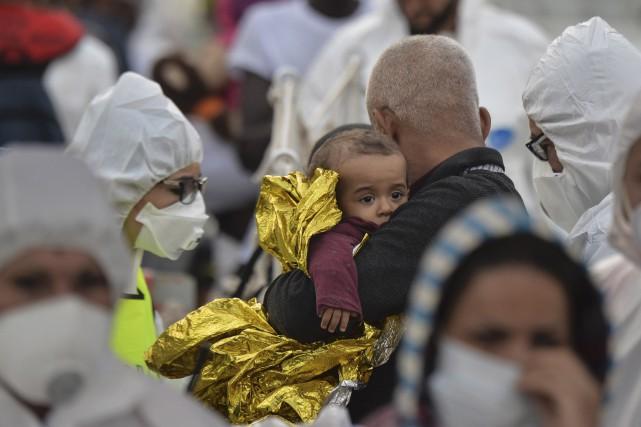Un homme serre un bébé dans ses bras... (AFP)