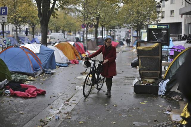 Une femme marche au milieu d'un campement de... (AP)