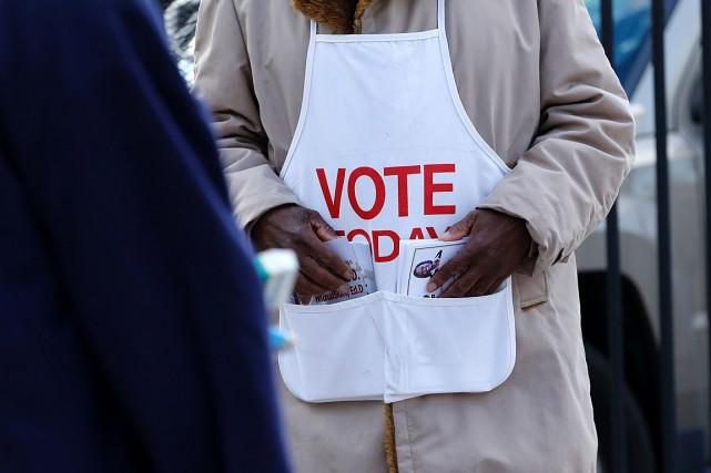 Un bénévole distribue des brochures d'information à l'extérieur... (PHOTO JEFF KOWALSKY, AFP)