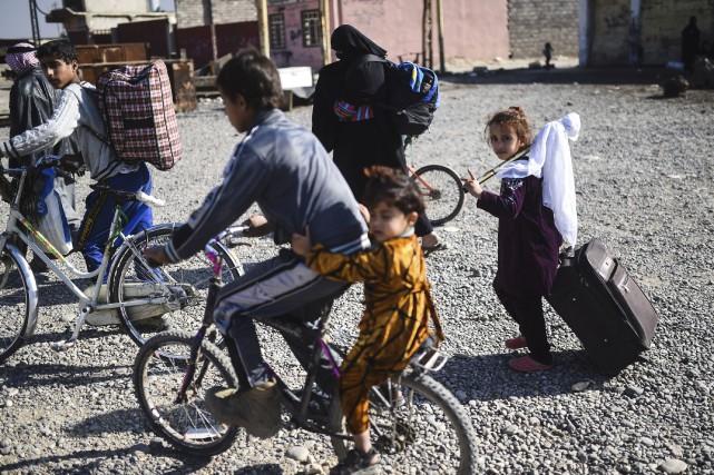 Des familles quittent Mossoul en brandissant un drapeau... (AFP)